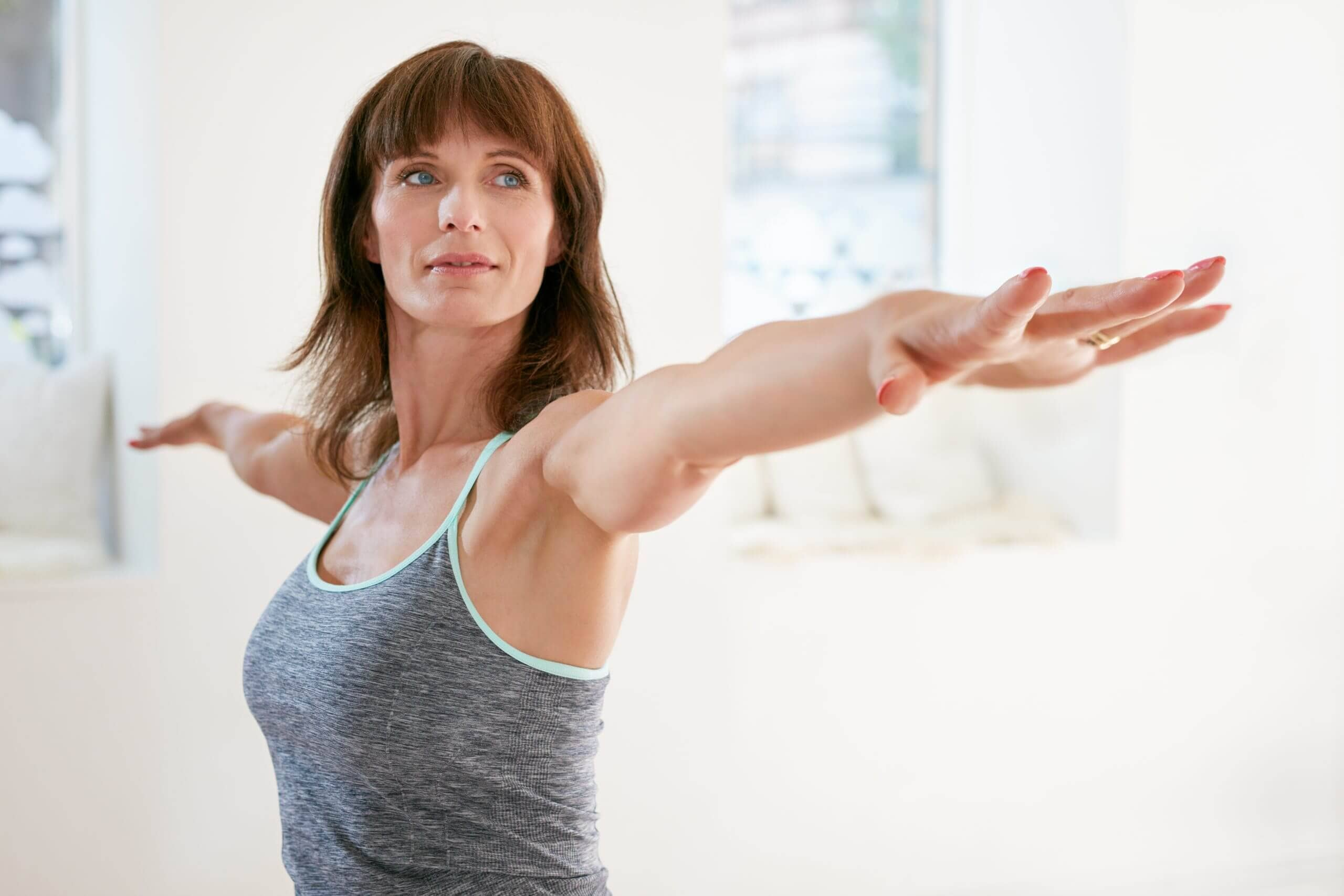 Woman performing yoga stretching her arms and looking away empower