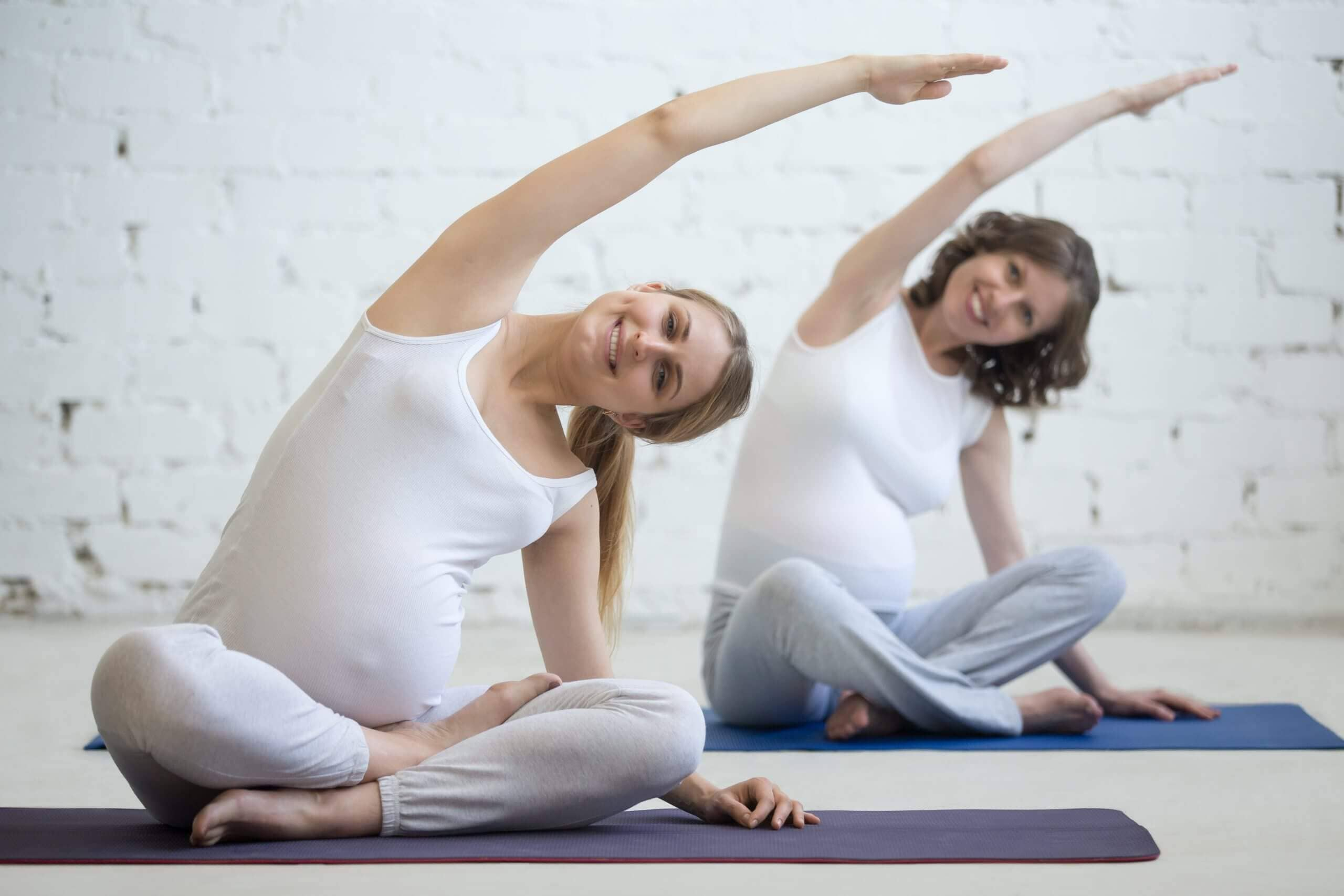 Pregnancy Yoga, Fitness concept. Two beautiful young pregnant yoga models working out indoor. Pregnant smiling fitness women sitting in yogic cross-legged pose at class. Prenatal sidebend in Easy Pose