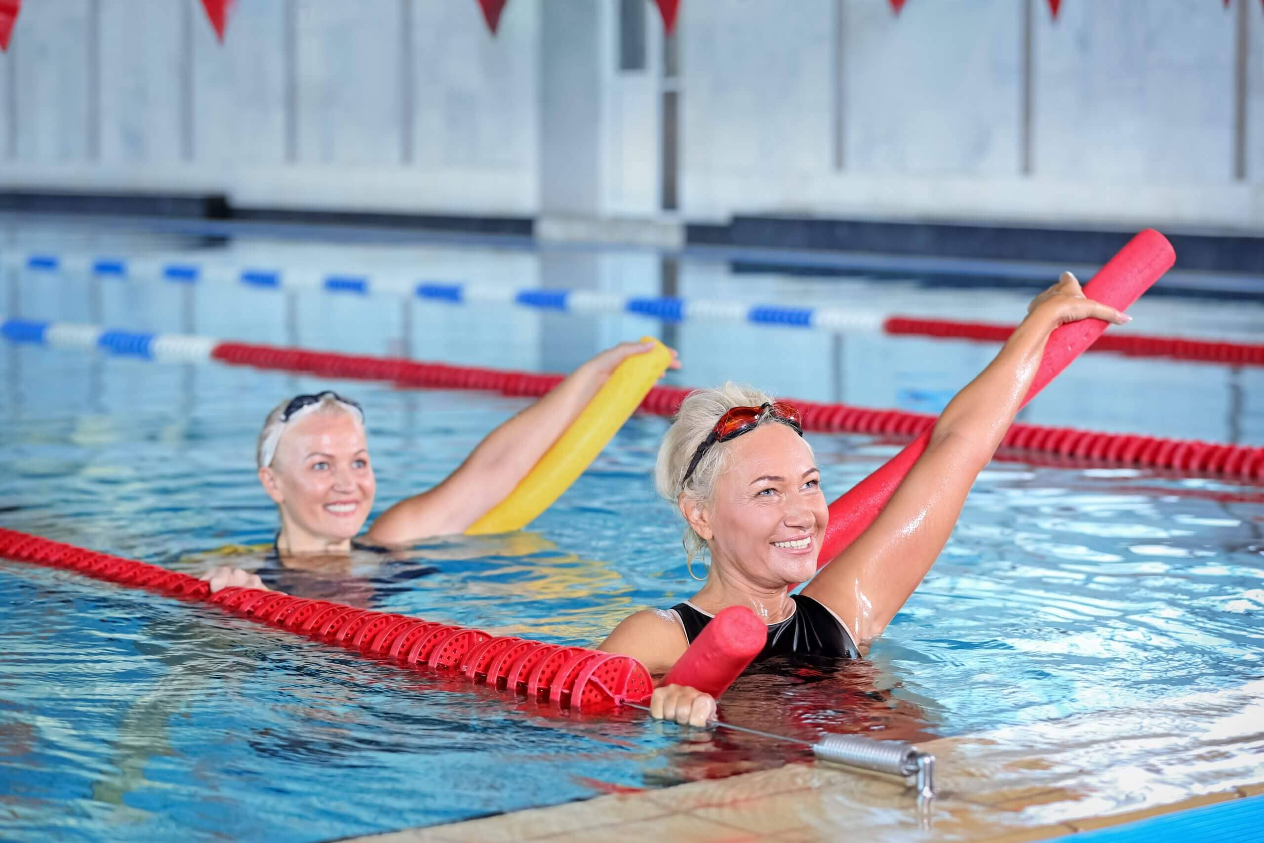 Sportive senior women doing exercises in indoor swimming pool